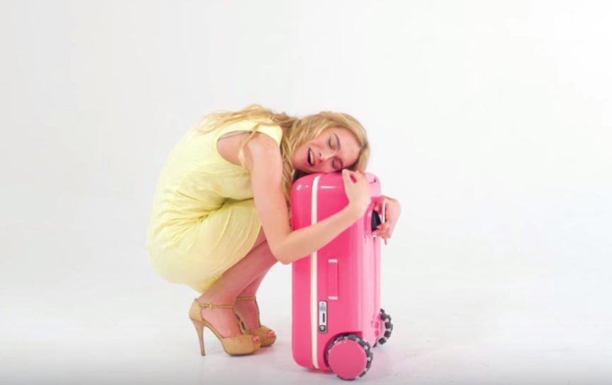 Woman hugging her suitcase, Travelmate Robotics, silicon valley, smart suitcase, robot suitcase, startups