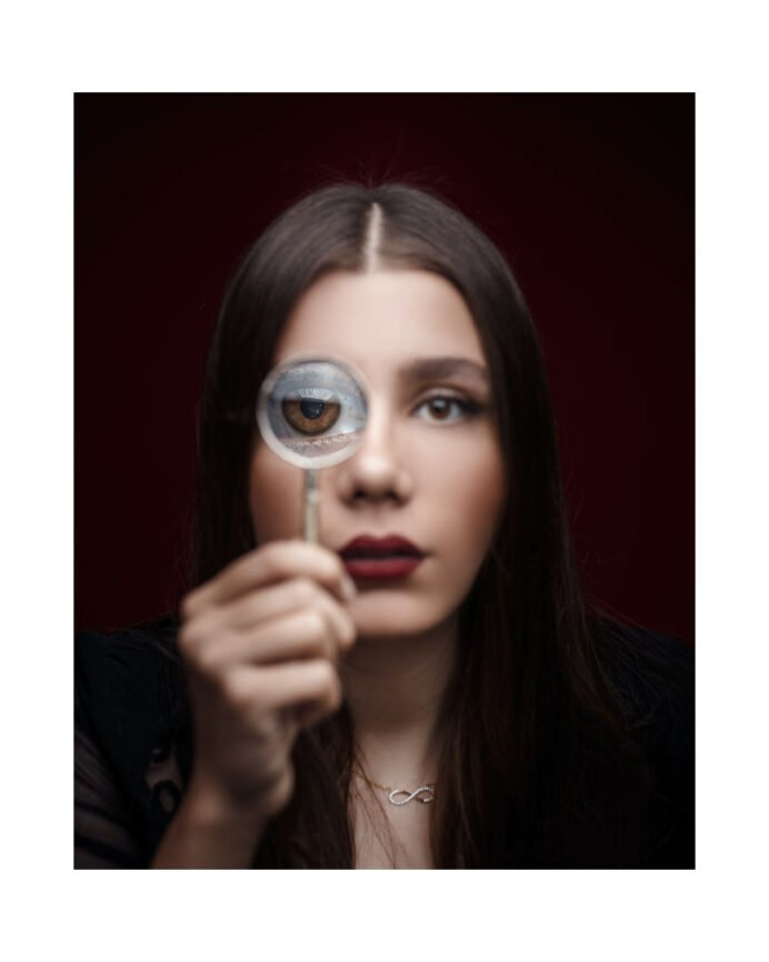 Dark haired woman looking through magnifying glass