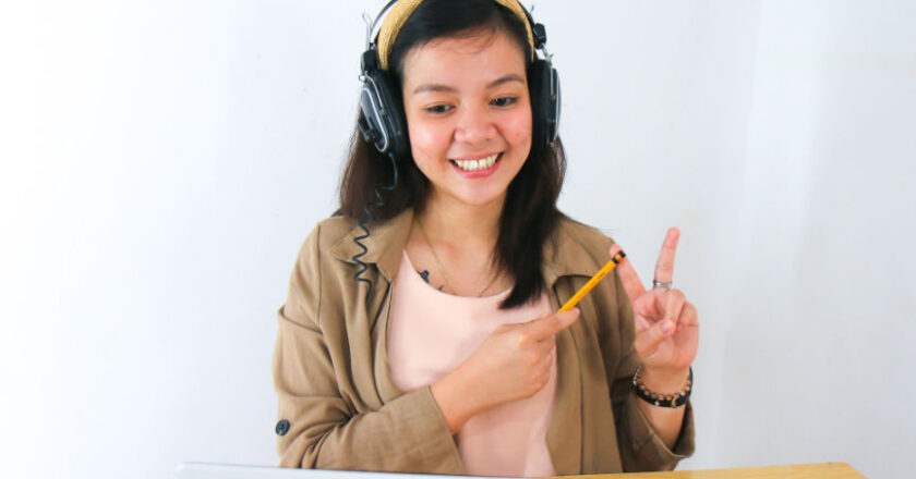 Girl at desk making peace sign with fingers in front of laptop