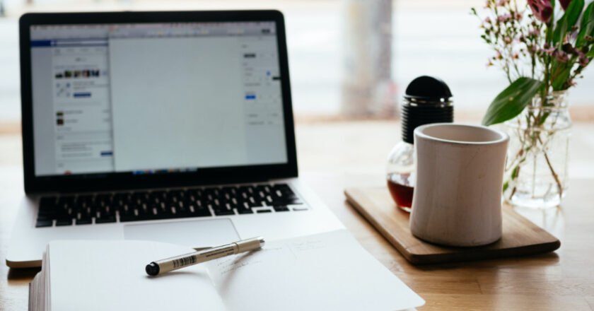Blank pages on laptop and notebook and cup of coffee on desk