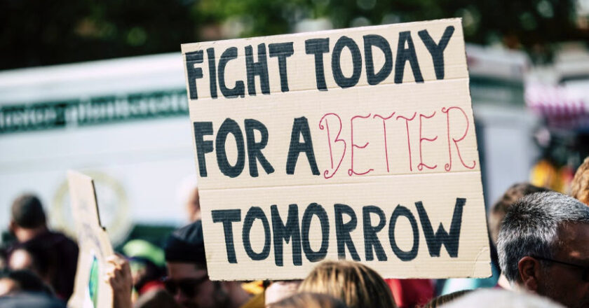 """Crowd holding sign that reads """"Fight Today For A Better Tomorrow"""""""