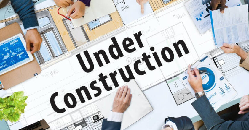 """People sitting around table with construction plans and a sign that reads """"Under Construction"""""""