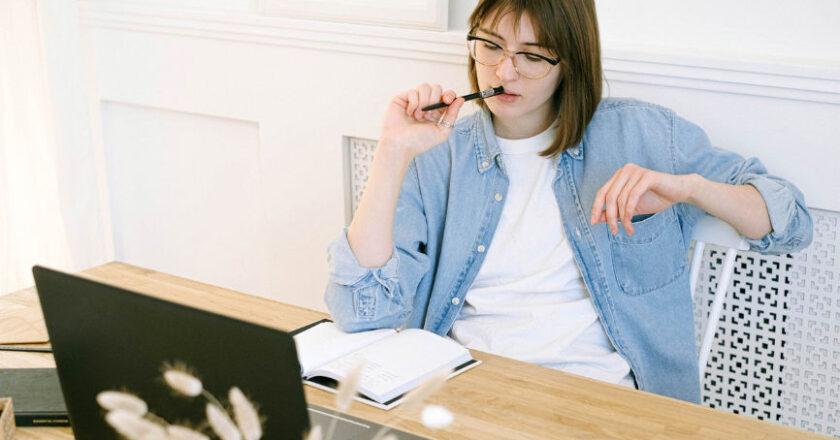 Female blogger sitting behind laptop, thinking