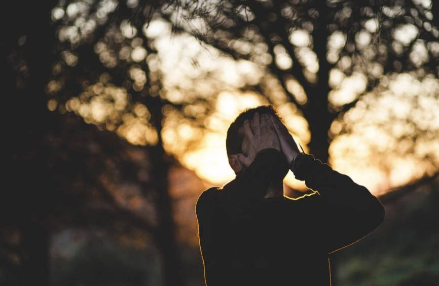 Stressed man covering face with hands