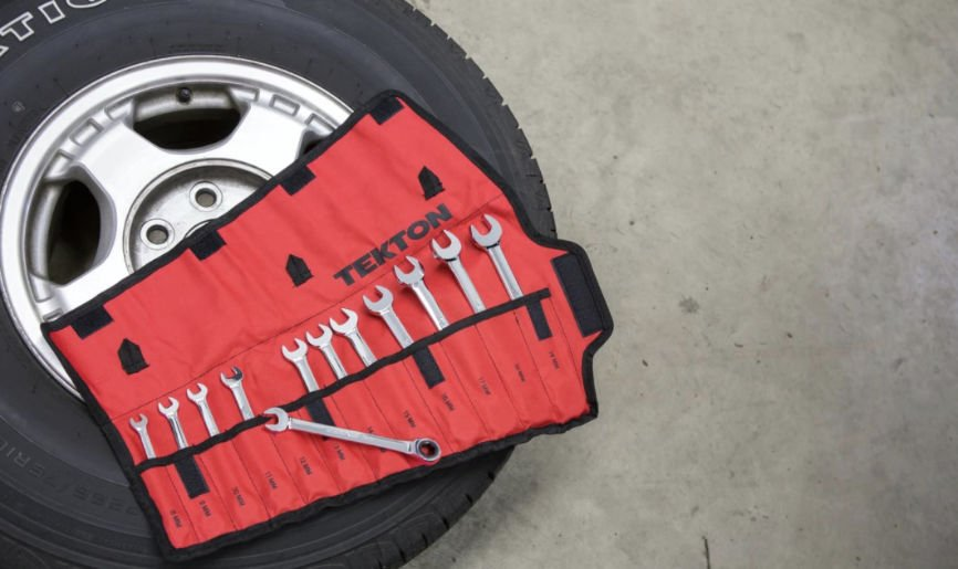 Set of wrenches sitting on a car tire