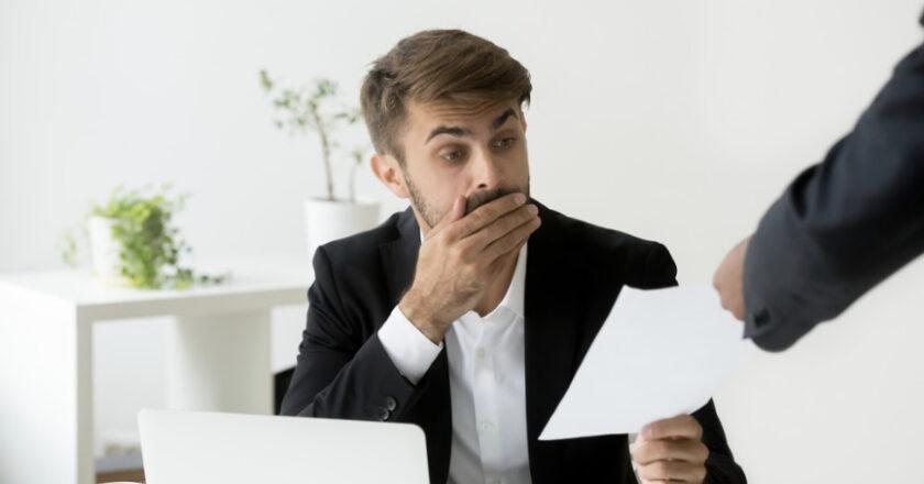 Man sitting at desk receiving a written warning