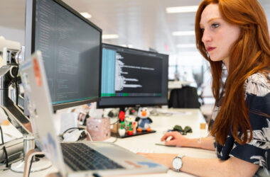 Woman developer seated at desk with multiple computer displays