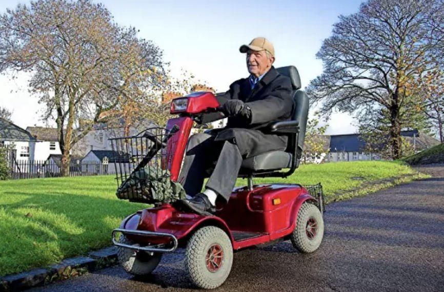 Senior citizen riding on a red electric scooter