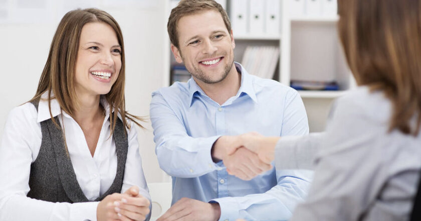 Couple smiling shaking hands with tax preparer