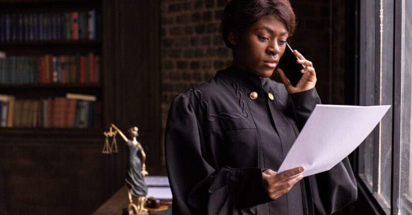 Female judge standing by a window, looking at a sheet of paper while on the phone