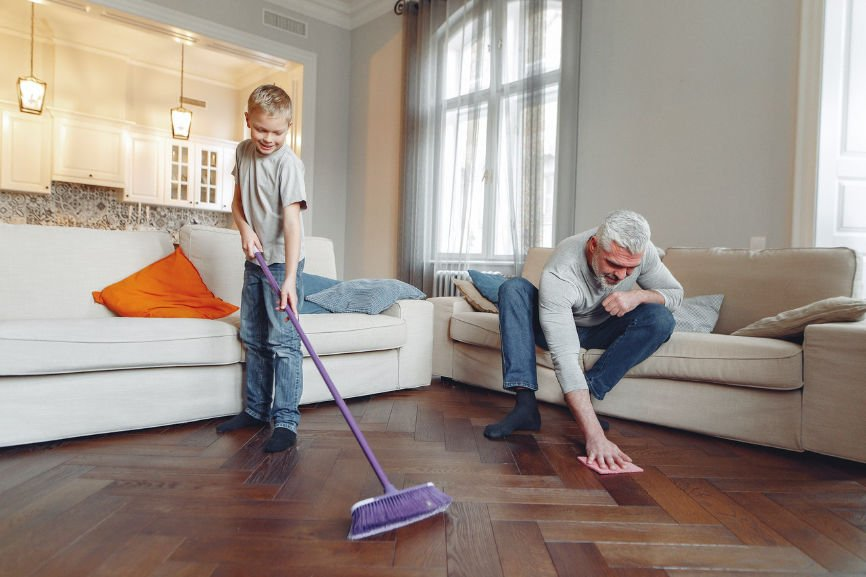 Young Boy and Senior Citizen Cleaning Wood Floor