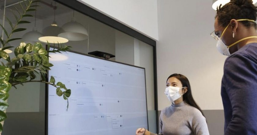 Man and Woman Studying information on a presentation screen