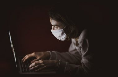 Masked person using laptop on online casino during pandemic