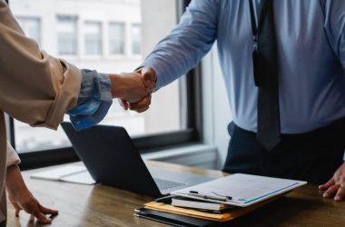 Two people shaking hands over a desk