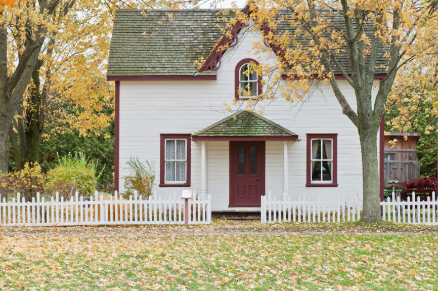 Small house with a white picket fence